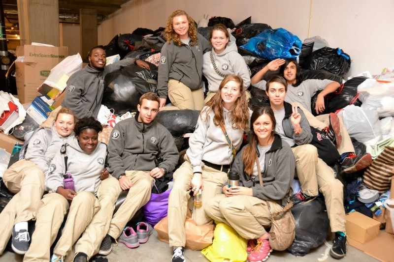 AmeriCorps volunteers by the massive pile of donations
